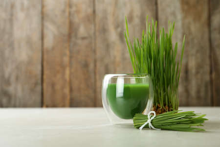 Glass of wheat grass juice and sprouts on table. Space for text Stock Photo - 124879072