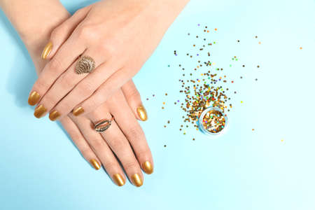 Woman showing manicured hands with golden nail polish and glitter on color background, top view