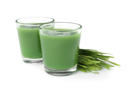 Glasses of fresh wheat grass juice and sprouts on white background Stock Photo
