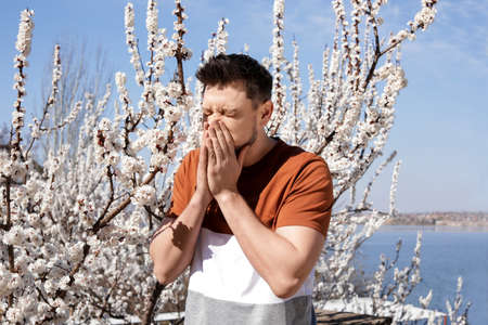 Man suffering from seasonal allergy outdoors on sunny day Imagens