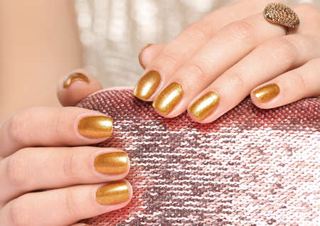 Woman holding manicured hands with golden nail polish on bag, closeup