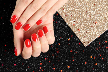 Woman showing manicured hands with red nail polish on color background, top view. Space for text