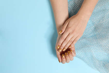 Woman showing manicured hands with golden nail polish on color background, top view. Space for text