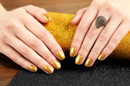 Woman showing manicured hands with golden nail polish on table, closeup Фото со стока - 124879230