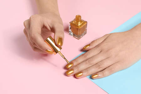 Woman painting nails with golden polish on color background, closeup