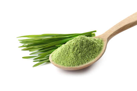 Wheat grass powder in wooden spoon and sprouts on white background