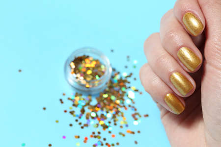 Woman showing manicured hand with golden nail polish over color background, closeup. Space for text