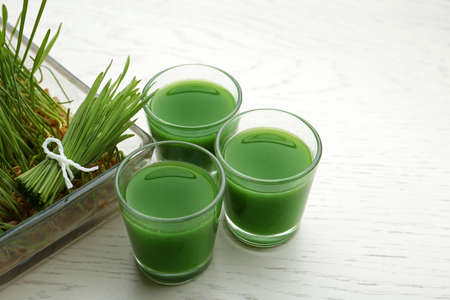 Glasses of wheat grass juice and sprouts on white wooden background Stock Photo