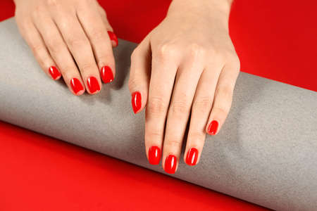 Woman showing manicured hands with red nail polish on color background, closeup Фото со стока - 124879288