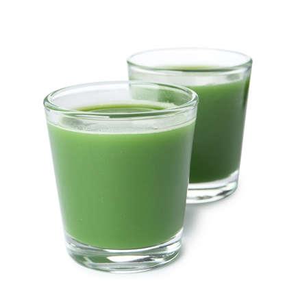 Jus d'herbe de blé frais dans des verres sur fond blanc