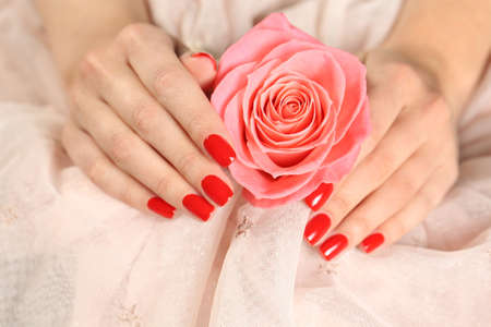 Woman holding manicured hands with red nail polish near rose on fabric, closeup
