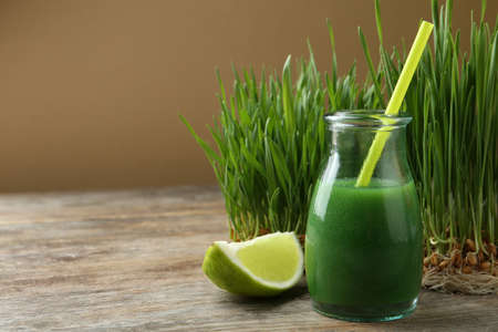 Glass bottle of wheat grass juice with citrus fruit and sprouts on wooden table. Space for text Stock Photo