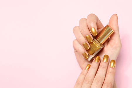 Woman holding bottle of golden nail polish in manicured hand on color background, top view. Space for text