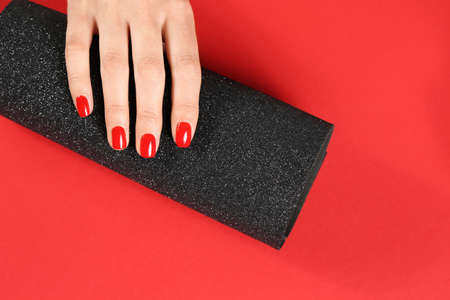 Woman showing manicured hand with red nail polish on color background, top view. Space for text Фото со стока
