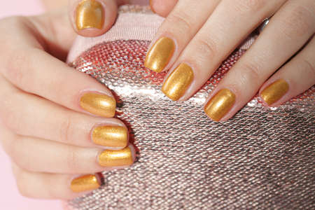 Woman holding manicured hands with golden nail polish on bag, closeup Фото со стока - 124879404