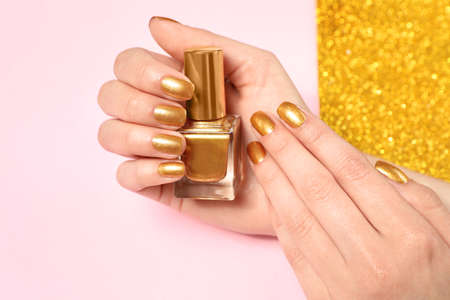 Woman holding bottle of golden nail polish in manicured hand on color background, closeup