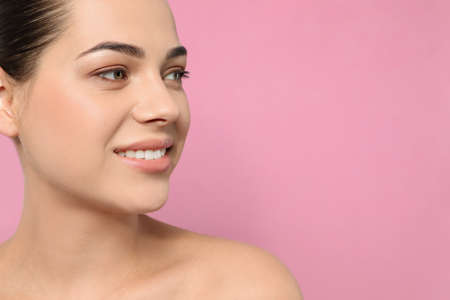 Portrait of young woman with beautiful face and natural makeup on color background, closeup. Space for text