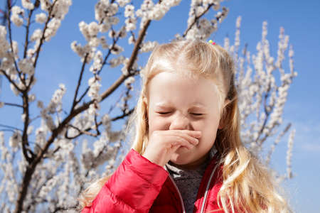 Little girl suffering from seasonal allergy outdoors Imagens