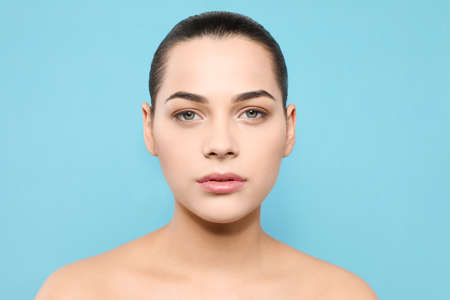Portrait of young woman with beautiful face and natural makeup on color background