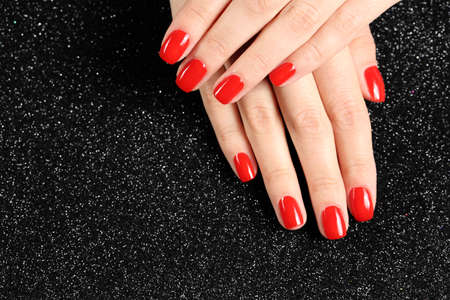 Woman showing manicured hands with red nail polish on black background, top view. Space for text Фото со стока