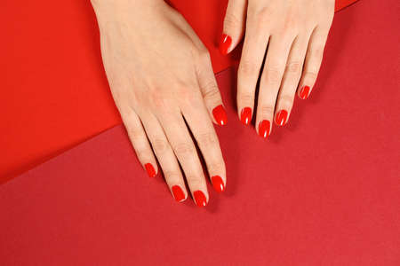 Woman showing manicured hands with red nail polish on color background, top view