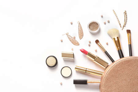 Cosmetic bag and different luxury makeup products on white background, top view