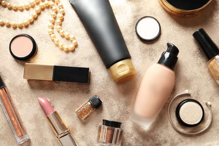 Different luxury makeup products on gold background, flat lay