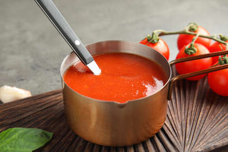 Pan with tomato sauce and spoon on wooden board, closeup Banco de Imagens