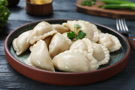 Plate of tasty dumplings served with parsley on table Reklamní fotografie