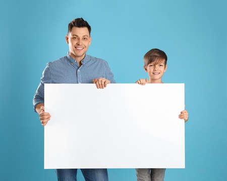 Dad and his son with empty banner on color background. Space for design