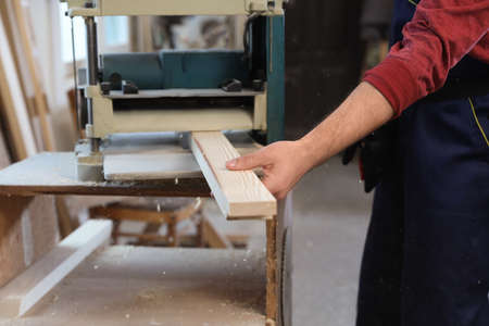 Working man using thickness planer at carpentry shop, closeup