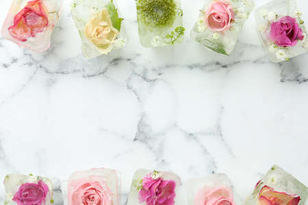 Ice cubes with flowers on marble background, flat lay. Space for text