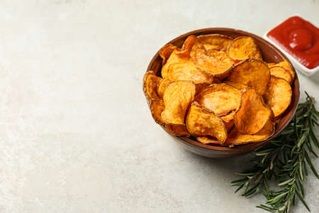 Delicious sweet potato chips in bowl, rosemary and sauce on light background. Space for text