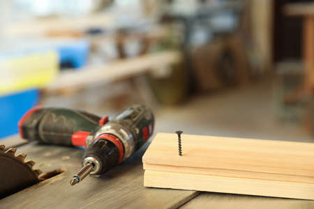 Carpenters working place with electric screwdriver and timber strip on table indoors Imagens