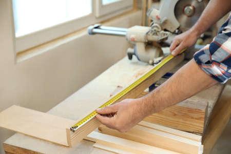 Working man measuring timber strip in carpentry shop, closeup