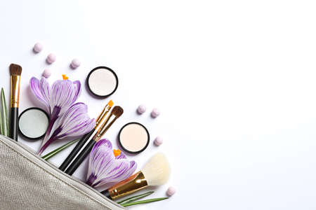 Makeup products, flowers and cosmetic bag on white background, top view Stock Photo