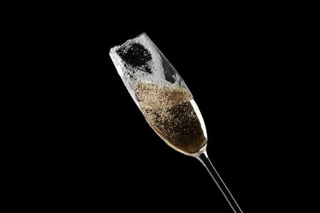 Glass of fizzy champagne on black background, closeup Stock Photo