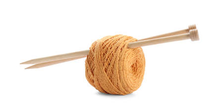 Clew of colorful thread with knitting pins on white background