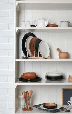Unidad de estantería blanca con juego de vajilla cerca de la pared de ladrillo Foto de archivo