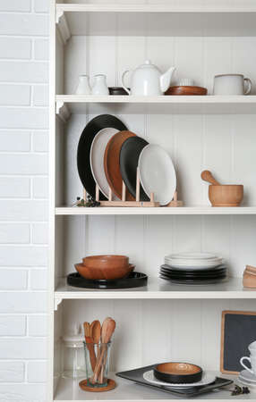 White shelving unit with set of dishware near brick wall Imagens