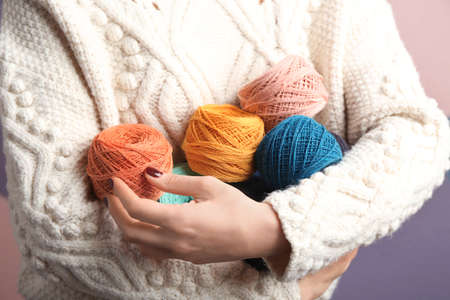 Woman holding clews of knitting threads, closeup