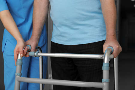 Nurse assisting senior patient with walker in hospital, closeup Banco de Imagens