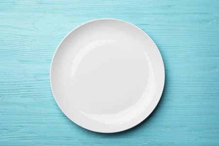 Stylish ceramic plate on wooden background, top view Standard-Bild - 124990518
