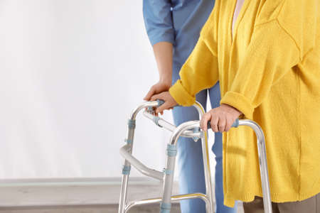 Nurse assisting senior woman with walker in hospital, closeup. Space for text