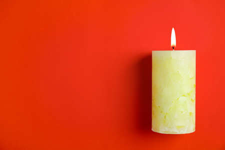 Alight wax candle and space for text on color background Stok Fotoğraf