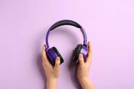 Woman holding stylish headphones on color background, closeup