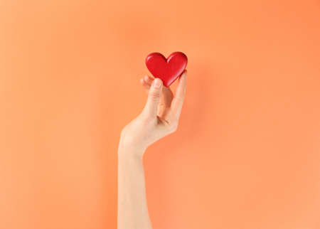 Woman holding decorative heart on color background, top view Reklamní fotografie
