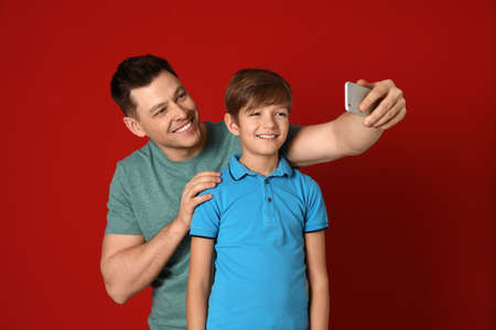 Dad and his son taking selfie on color background