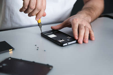 Technician repairing mobile phone at table, closeup