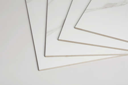 Stack of ceramic tiles on white background. Space for text
